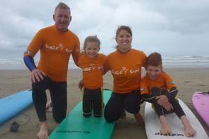 a family pause from their surf lesson for a family photo